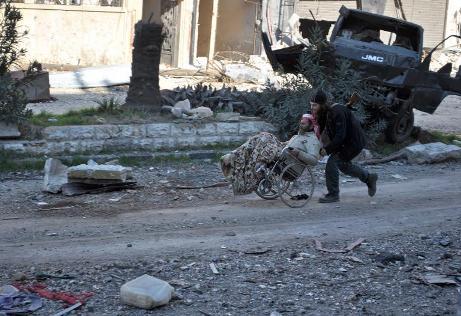 أحد المسلحين في داخل مدينة حمص يساعد رجلاً مقعداً على اللحاق بالمدنيين المغادرين للمدينة-الصورة من وكالة الأنباء الفرنسية