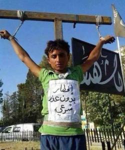 طفل قامت داعش بإعدامه وتعليق جثته في الرقة لإفطاره بدون عذر في رمضان، كما تقول اللوحة المعلقة على جثمانه
