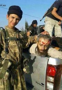طفل يحمل رأس القاضي الشرعي العام لألوية صقور الشام بعدما قامت داعش بذبحه