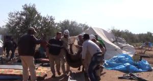 رجال الدفاع المدني ينقلون الضحايا من المخيم بعد المجزرة