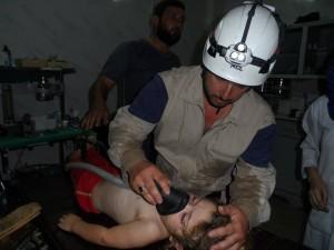 عناصر من الدفاع المدني يحاولون إسعاف طفل أصيب أثناء الغارة على سرمين