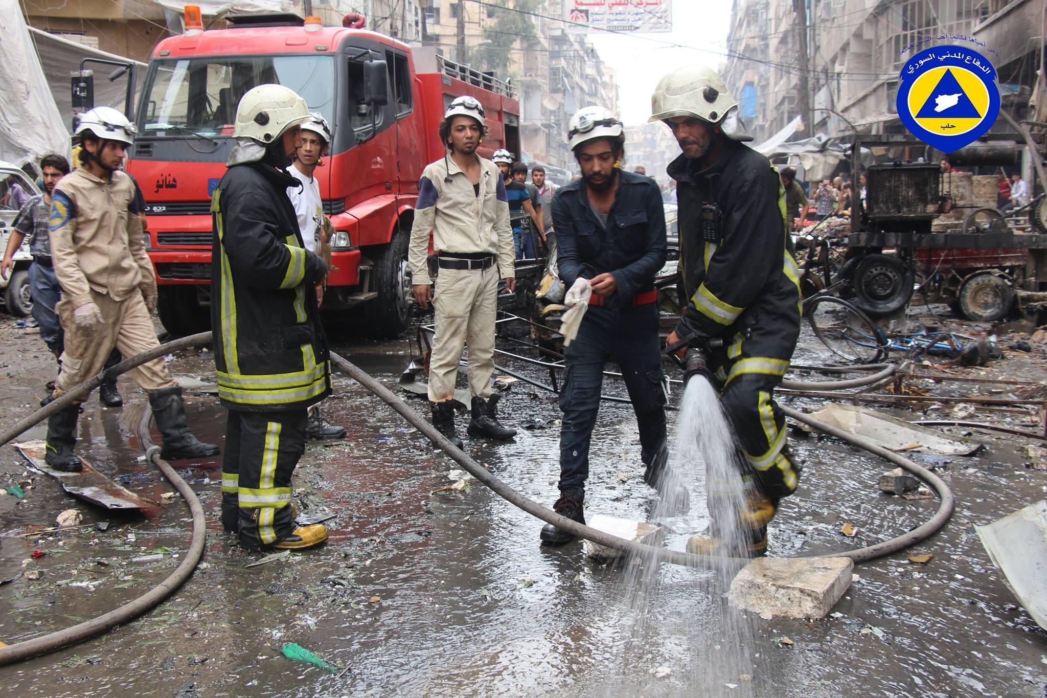 عناصر الدفاع المدني يقومون بإطفاء الحرائق الناجمة عن القصف على السوق