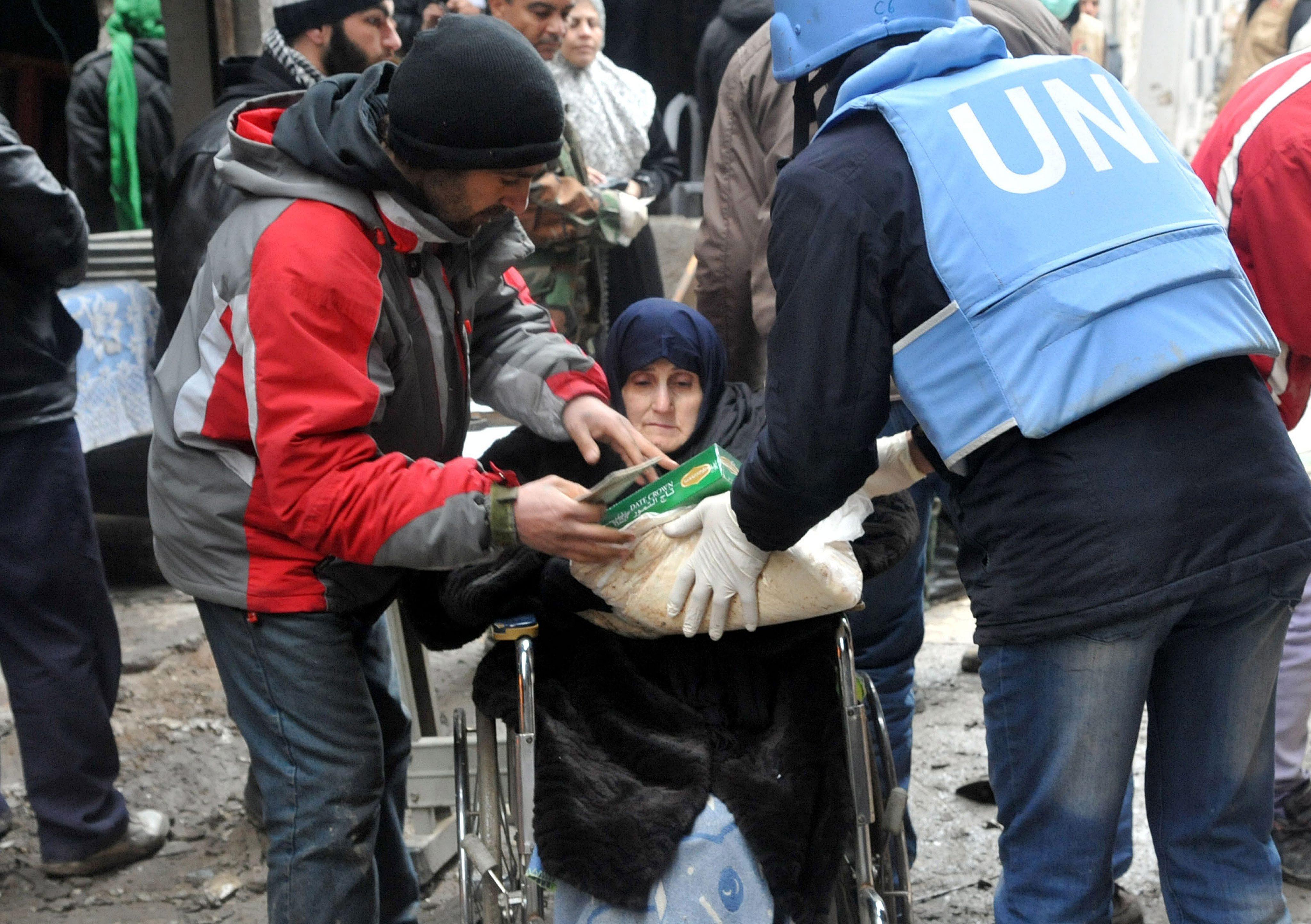 الصورة بتاريخ 4/2/2014 لموظف من الأمم المتحدة يقدم مساعدات لسيدة مسنة في مخيم اليرموك في دمشق
