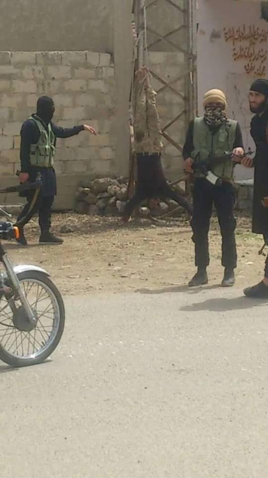 عناصر  شهداء اليرموك وحركة المثنى  يقفون أمام إحدى الجثث التي تم تعليقها