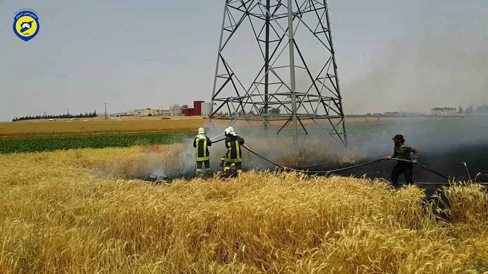 عناصر الدفاع المدني يقومون بإطفاء الحرائق في الأراضي الزراعية في ريف حلب الغربي نتيجة للقصف العنقودي