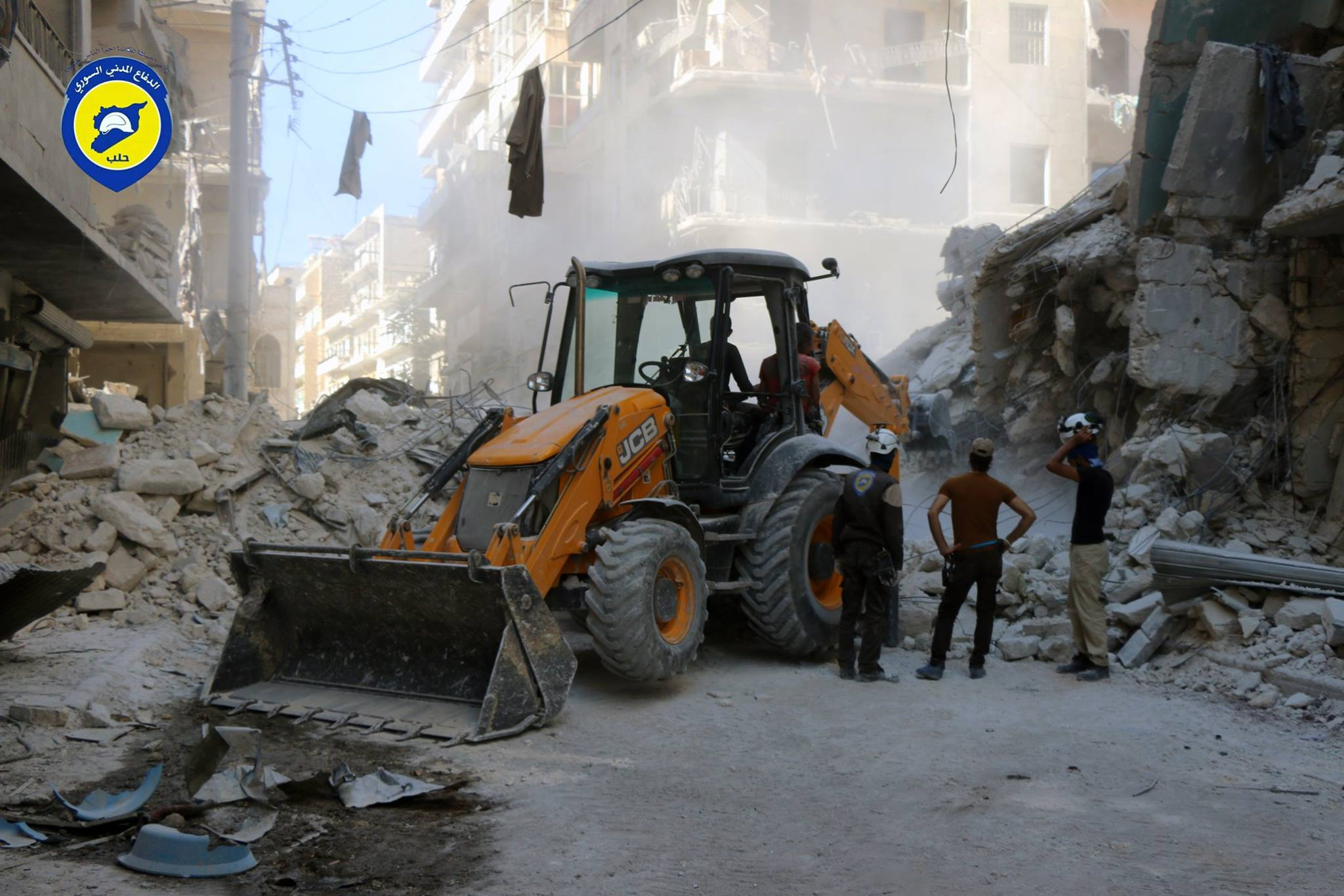 عناصر الدفاع المدني يقومون برفع الأنقاض في الحي بعد الغارات
