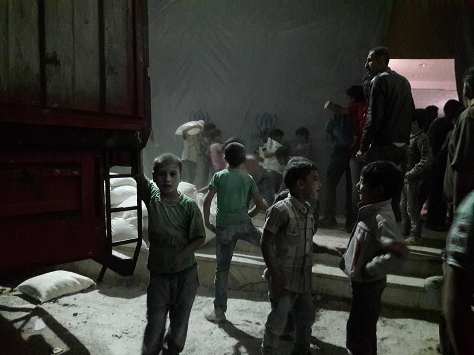 أطفال في مضايا يقومون بتفريغ المواد الغذائية من شاحنات المساعدات
