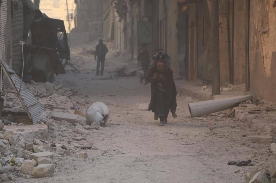 رجل يحمل والدته المسنة لمساعدتها على النزوح في حلب الشرقية