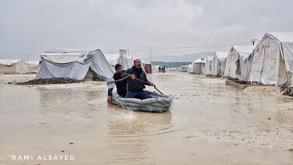 نازحون في مخيم دير بلوط يستخدمون قارباً داخل المخيم، بعد أن غمرته المياه يوم الأربعاء